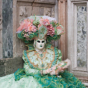 VENICE, ITALY - FEBRUARY 11:  A woman wearing a Carnival costume poses for pictures while sitting on the steps of Palazzo Ducale in St. Mark's Square on February 11, 2012 in Venice, Italy.The annual festival, which lasts nearly three weeks, will see the streets and canals of Venice filled with people wearing highly-decorative and imaginative carnival costumes and masks.
