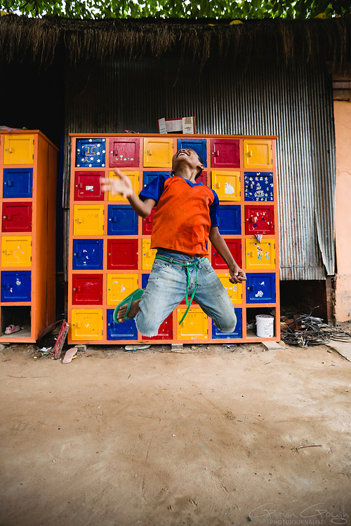 A boy jumping and laughing in front of clothes lockers with bright, colourful doors, ACODO, Siem Reap, Cambodia