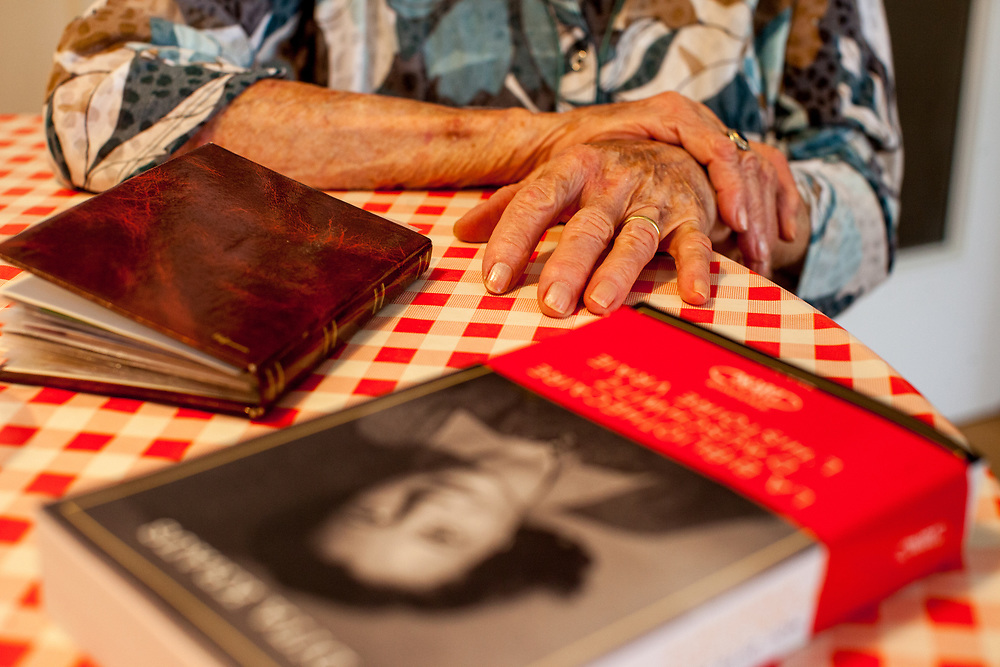 """Dita Kraus hands and infront the french edition of her book in her flat in Prague Vinohrady. Born in Prague to a Jewish family in 1929, Dita Kraus has lived through the most turbulent decades of the twentieth and early twenty-first centuries. Here, Dita writes in her book """"A Delayed Life: The true story of the Librarian of Auschwitz"""" with startling clarity on the horrors and joys of a life delayed by the Holocaust. From her earliest memories and childhood friendships in Prague before the war, to the Nazi-occupation that saw her and her family sent to the Jewish ghetto at Terezín, to the unimaginable fear and bravery of her imprisonment in Auschwitz and Bergen-Belsen, and life after liberation."""