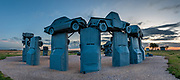 """Evening twilight at Carhenge, Alliance, Nebraska, High Plains region, USA. Carhenge replicates England's Stonehenge using vintage American automobiles, near Alliance. After studying Stonehenge in England, years later, Jim Reinders recreated the physical size and placement of Stonehenge's standing stones in summer 1987, helped by 35 family members. Reinders said, """"It took a lot of blood, sweat, and beers."""" Carhenge was built as a memorial to Reinders' father. 39 automobiles were arranged in the same proportions as Stonehenge with the circle measuring a slightly smaller 96 feet (29m) in diameter. Some autos are held upright in pits five feet deep, trunk end down, while other cars are placed to form the arches and welded in place. All are covered with gray spray paint. The heel stone is a 1962 Cadillac. Reinders donated Carhenge to the Friends of Carhenge, who gifted it to the Citizens of Alliance in 2013. Additional sculptures have been erected in the Car Art Reserve, where Reinders' """"Ford Seasons"""" is comprised of four Fords, inspired by Vivaldi's Four Seasons. Also, 29-year-old Canadian Geoff Sandhurst sculpted a spawning salmon. This image was stitched from multiple overlapping photos."""
