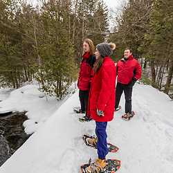 A man and three kids snowshoe on a bridge over the Hudson River near Henderson Lake on the Tahawus Tract, Newcomb, New York. Adirondack Mountains.
