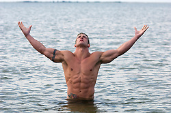 bodybuilder with a tattoo standing waist deep in water with his head and arms raised to the sky