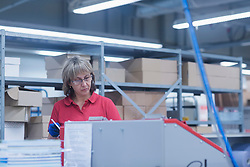 Mature woman working in books printing industry, Bremgarten, Hartheim am Rhein, Baden-W¸rttemberg, Germany