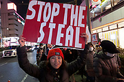 """A Japanese woman, holds a sign reading Stop the Steal as several hundred people, taking part in a """"March For Trump"""" rally  in support of the out-going United States President, Donald Trump. Tokyo, Japan. Wednesday January 6th 2021. The rally of mostly Japanese people took place as part of a similar rally by Trump-supporters in Washington DC as the results of the 2020 US Presidential election were confirmed."""