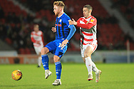 Callum Camps is challenged by Tommy Rowe during the EFL Sky Bet League 1 match between Doncaster Rovers and Rochdale at the Keepmoat Stadium, Doncaster, England on 1 January 2019.