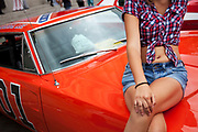 Actor playing Daisy Duke sits on the bonnet of the famous car used in the hit American movie and tv show The Dukes of Hazard. This car, a 2 door coupe style muscle car, was the Chrysler produced Dodge Charger. The General Lee as that car was known was adorned with the number 01.