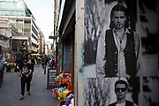 Street Scene on Berwick Street in Soho showing an old photo of Bono from U2 as a paste up poster, London, England, United Kingdom.