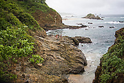 Two local fisherman stand on the rocky shore of a small cove along the coast near the village of Mazunte, Oaxaca, Mexico on July 7, 2008.