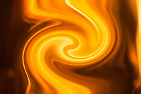 fluid fire flame with yellow and orange shades on dark blurred background