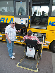Wheelchair used and helper using lift to get onto coach