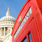 One of London's famous red phone boxes with the dome of St Pauls Cathedral in the background.