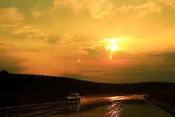 Um carro em viajem contempla um lindo por-do-sol na estrada após a chuva. FOTO: Jefferson Bernardes/Preview.com