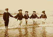 French coastal scene with children on a beach. Circa 1900