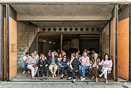 A group of women waits for the procession to pass in their street. Men play cards in the back of a garage in Cordoba. Andalusia, Spain