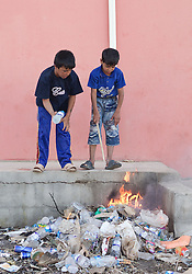 © Licensed to London News Pictures. 25/06/2014. Khanaqin, Iraq. Two young Iraqi refugees play with burning rubbish at a refugee camp on the outskirts of Bahari Taza village in Iraq. Located on the outskirts of Khanaqin, a town just 20 minutes from the front-line of the battle with ISIS insurgents, the Bahari Taza refugee camp, and its satellite camps, now house around 600 families from southern Iraq. Built by the local village leader to meet the influx of refugees from nearby Jalawla and Saidia, where intense fighting is still taking place. Turkman, Arab and Kurd, both Sunni and Shia, all live together in tents, barns and unfinished buildings waiting for the conflict to end. Photo credit: Matt Cetti-Roberts/LNP
