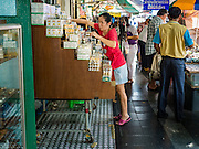 29 NOVEMBER 2015 - BANGKOK, THAILAND:  A woman sells traditional ointments in a street stall in the Amulet Market on Maharat Road in Bangkok. Hundreds of vendors used to sell amulets and Buddhist religious paraphernalia to people in the Amulet Market, a popular tourist attraction along Maharat Road north of the Grand Palace near Wat Maharat in Bangkok. Bangkok municipal officials announced that they are closing the market and forcing vendors to relocate to an area about one hour outside of Bangkok. The closing of the amulet market is the latest in a series of municipal efforts to close and evict street vendors and markets from areas that have potential for redevelopment. The street vendors were evicted from the area on Sunday, Nov. 29.      PHOTO BY JACK KURTZ