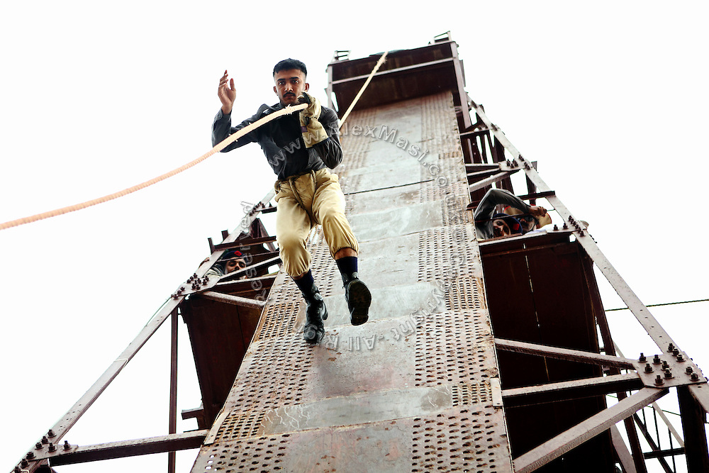 A recruit of the Shaheed Benazir Bhutto Elite Police Training Center, a commando and anti-terrorism academy on the outskirts of Karachi, is exercising and simulating an extreme action on a high tower located on the premises. The training center was founded by retired colonel Abdul Wahid Khan, a brave officer who served as a gunship helicopter pilot in the Pakistani Air Force and around the globe with the United Nations, but who's first task as a young army officer in 1979 was to train Afghan Mujahedeen to fight the Soviet Army, the very Mujahedeen that are today's Taleban.