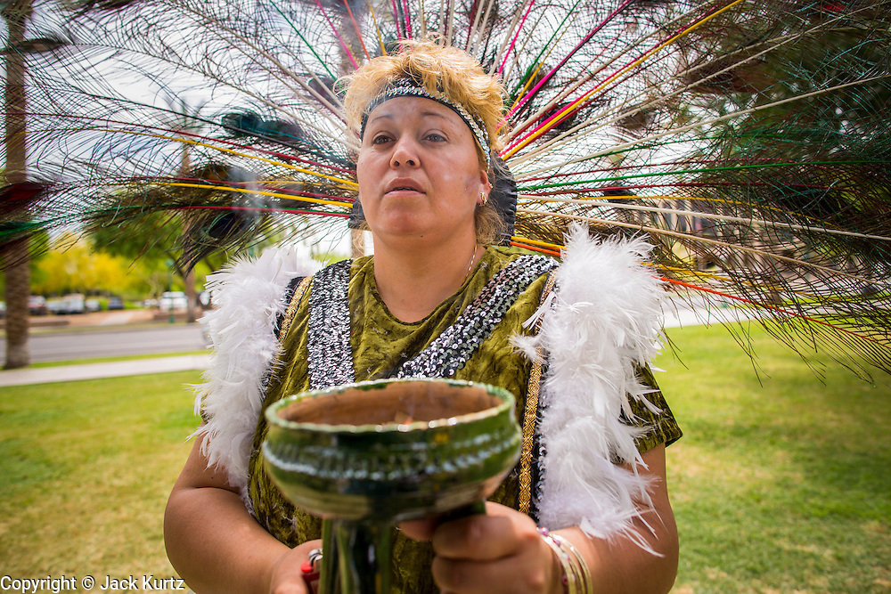 25 APRIL 2012 - PHOENIX, AZ:  PATTY SALDANA, from Phoenix, holds incense during a prayer vigil against SB1070 at the Arizona state capitol Wednesday. Immigrants' rights groups opposed to SB1070 and Tea Party affiliated groups that support SB1070 gathered at the state capitol in Phoenix Wednesday to express their opposition and support of the bill. SB1070 was signed by Arizona Governor Jan Brewer in April 2010. At the time it was the toughest anti-illegal immigration bill in the country. Immigrants' rights groups sued Arizona and the federal courts stopped enforcement of the bill. The bill ended up in the US Supreme Court which heard arguments Wednesday. A ruling on the bill is expected in June.   PHOTO BY JACK KURTZ