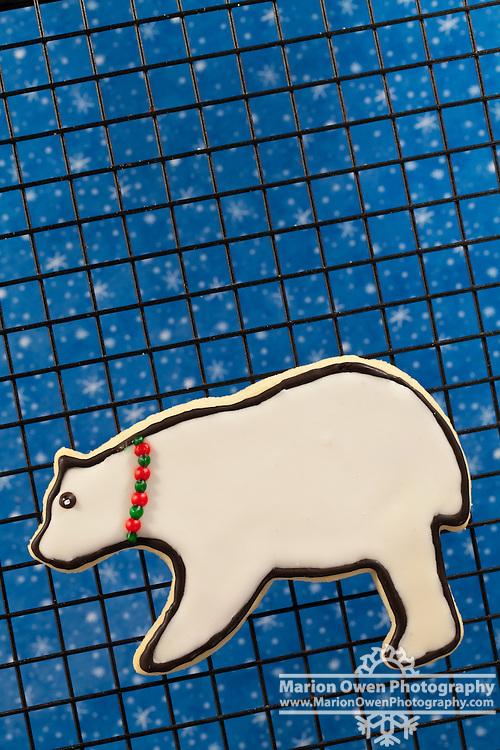 Closeup of Christmas, polar bear sugar cookie polar bear decorated with a green and red collar.