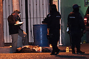 A police investigator examines the body of a man slain by cartel assigns as he went to visit his relatives in Juarez, Mexico January 14, 2009. The shooting, believed linked to the ongoing drug war which has already claimed more than 40 people since the start of the year. More than 1600 people were killed in Juarez in 2008, making Juarez the most violent city in Mexico.    (Photo by Richard Ellis)