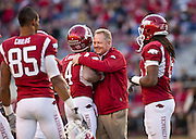 Nov 5, 2011; Fayetteville, AR, USA;  Arkansas Razorback head coach Bobby Petrino, second from right, hugs wide receiver Jarius Wright (4) as wide receivers Greg Childs (85) and Keante Minor (15) look on before the start of a game against the South Carolina Gamecocks at Donald W. Reynolds Stadium.  Mandatory Credit: Beth Hall-US PRESSWIRE