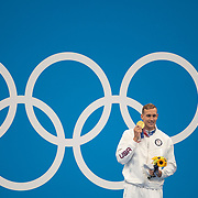 TOKYO, JAPAN - JULY 31:   Caeleb Dressel of the United States with his gold medal on the podium after winning the 100m Butterfly Final for men during the Swimming Finals at the Tokyo Aquatic Centre at the Tokyo 2020 Summer Olympic Games on July 31, 2021 in Tokyo, Japan. (Photo by Tim Clayton/Corbis via Getty Images)
