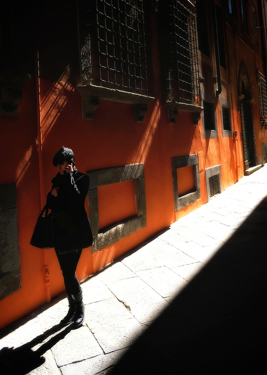 Image of a woman on cell phone exiting a dramatically lit alley in Lucca, Italy.