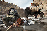 A caravan leader named Shoh Nawoz takes a drink of water out of a hole in teh ice..Trekking up the Wakhan frozen river, the only way up to reach the high altitude Little Pamir plateau, home of the Afghan Kyrgyz community.