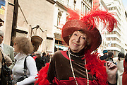A woman wearing a hat and stole adorned with red feathers.