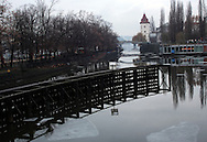 A view downt the river vltava in the czech republic during  winter, with the ice flakes floating around on the water, and the tree's and the restaurant by the river mirroring in the water. In the background view to a white water tower and one of Prague's many Bridges