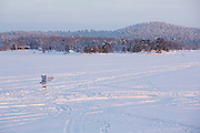 Signpost in Lake Inari to indicate directions to various locations for snowmobiles and other transport across the ice.