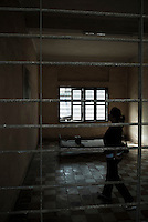A visitor inside a VIP cell in Building A at Tuol Sleng Genocide Museum, Phnom Penh, Cambodia