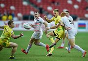 Australia's Tom Kingston off-loads the ball during the HSBC World Rugby Sevens Series - Singapore, Bronze match Australia-V-England at The National Stadium, Singapore on Sunday, April 16, 2017. (Steve Flynn/Image of Sport)