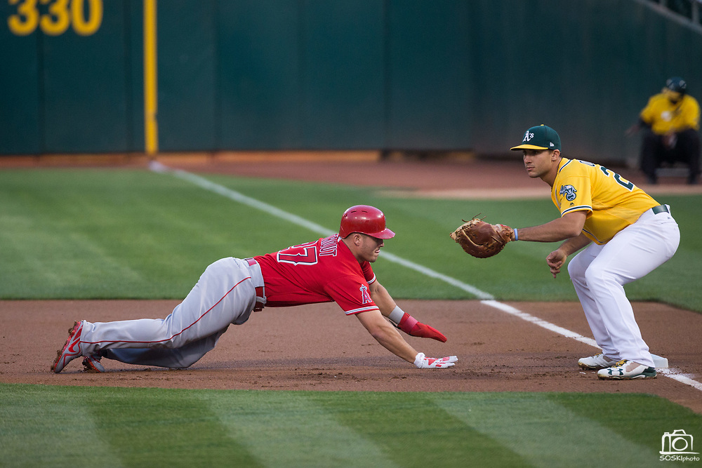 Los Angeles Angels center fielder Mike Trout (27) dives back to first base as Oakland Athletics first baseman Matt Olson (28) catches a pick off attempt throw at Oakland Coliseum in Oakland, California, on September 5, 2017. (Stan Olszewski/Special to S.F. Examiner)
