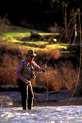 Stock photo of a man fly fishing in a flowing river