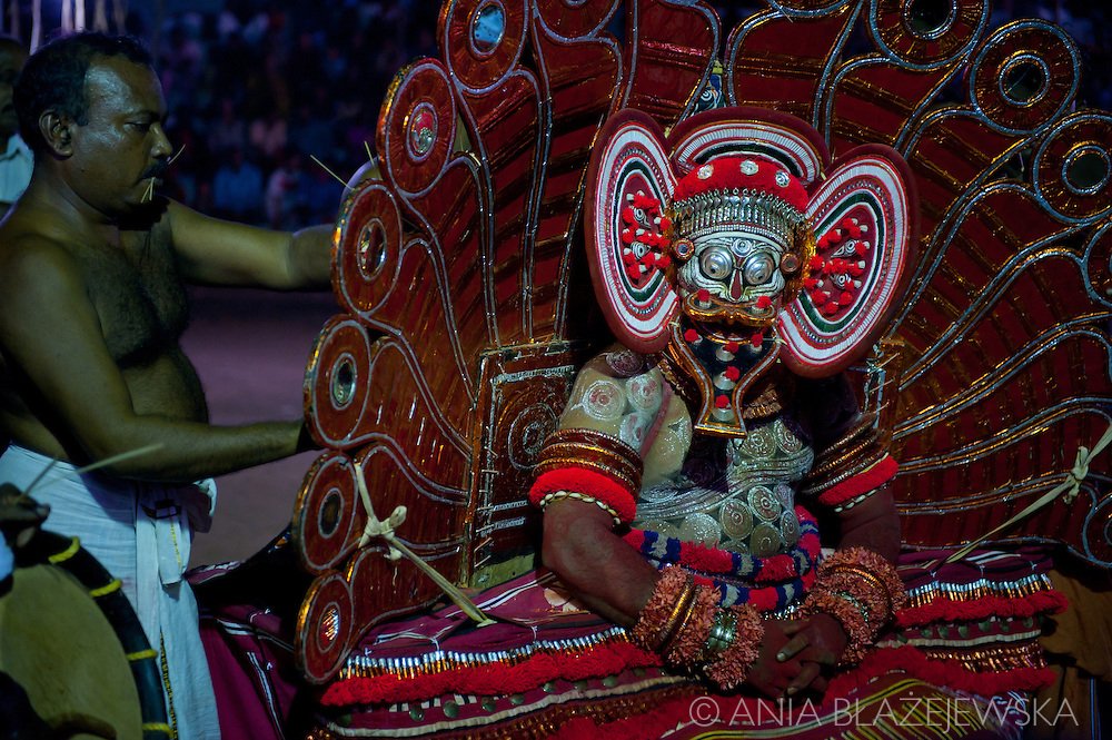 Theyyam is the ancient hindu ritual of North Malabar in Kerala in which empowered men after suitable preparations become deities. It's the living cult with several thousand-year-old traditions and a socio-religious ceremony which attributes great importance to the worship of heroes and ancestral spirits. <br /> <br /> Wearing outstanding costumes and headdresses and with their human faces hidden behind fabulous masks the chosen men make the final change into the deities. When the line is crossed, comes the time for devotees to pray and speak to the deities.