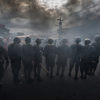 A row of soldiers confront protestors in clouds of smoke from burning tyres on barricades. The protest was against electoral fraud by the Nationalist Party.