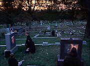 "FINAL CONTACT: ""GRAVEWATCH"".  Photo Illustration for the Future of Communication GEO (Germany) Special issue. Fictional Representation and Caption: Interactive gravestones became quite popular in the 21st century. Adding snippets of video of the diseased was quite easy to program since nearly every family had extensively documented their family time with small digital videocams. AI (artificial intelligence) computer programs made conversations with the dead quite easy. These virtual visits to the underworld became passé within a decade however, and graveyard visits became less common. By mid-century many people wanted to insure that their relatives would continue paying their respects, and keeping their memory alive. New technology insured regular visits to the gravesite to pick up a monthly inheritance check issued electronically by a built-in device with wireless connection to the living relative's bank account. Face recognition (and retinal scanners on high-end models) insured that family members were present during the half-hour visits. A pressure pad at the foot of the grave activated the system and after 30 minutes of kneeling at the grave, watching videos or prerecorded messages or admonitions, a message flashed on the screen, indicating that a deposit had been made electronically to their bank account. For the Wright family of Napa, California, there is no other way to collect Uncle Eno's inheritance other than by monthly kneelings. [""Gravewatch"" tombstones shown with ""Retscan"" retinal scanning ID monitors.] MODEL RELEASED"