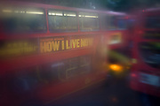 Seen through upper-deck window condensation, buses and traffic during damp, gloomy weather in central London.