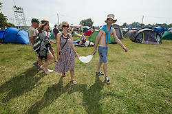 © Licensed to London News Pictures. 18/07/2014. Southwold, UK.   Festival goers carry bags of ice on a hot sunny morning at Latitude Festival 2014 Day 1. Today is expected to be the hottest day of the year with temperatures forecast to reach 32 degrees centigrade.   Latitude is an British annual music festival.  Photo credit : Richard Isaac/LNP