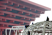 Workers construct a steel structure in front of the China Pavilion at the 2010 Expo site in Shanghai, China on 22 January 2010.  Shanghai eventually spent some 40 billion usd in developing the expo site and related infrastructure, and saw a record breaking 70 million visitors, the site has seen limited use after the end of the expo.