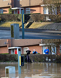 © Licensed to London News Pictures. 27/12/2016. York, UK. Side by side comparison pictures showing residents on Huntington Road in York as it is today, December 27, 2016 (TOP), and exactly a year ago today, on December 27, 2015 (BOTTOM) during the middle of severe flooding. Homes and businesses were destroyed in the flooding over the Christmas period last year. Photo credit: Ben Cawthra/LNP