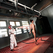 A humorous look at the spray tan industry with a naked model getting a spray tan in an industrial paint shop.