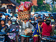 11 OCTOBER 2016 - UBUD, BALI, INDONESIA:   A man carries his market purchases down on Jalan (Street) Raya Ubud as he leaves the morning market. The morning market in Ubud is for produce and meat and serves local people from about 4:30 AM until about 7:30 AM. As the morning progresses the local vendors pack up and leave and vendors selling tourist curios move in. By about 8:30 AM the market is mostly a tourist market selling curios to tourists. Ubud is Bali's art and cultural center.    PHOTO BY JACK KURTZ