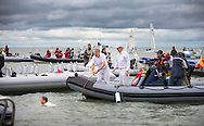 The first players make their way onto the 'pitch' while the tide slowly recedes for the annual Bramble Bank cricket match in the middle of the sea. The eccentric game involves members of the Royal Southern Yacht Club in Hamble playing against the Island Sailing Club from Cowes on the Brambles, a patch of sand in the Solent, only visible for a few minutes on the spring tide. The teams take turns in winning. This year the Royal Southern team won and hosted dinner at their club house.<br /> Picture date Monday 31st August, 2015.<br /> Picture by Christopher Ison. Contact +447544 044177 chris@christopherison.com