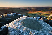 A frost circle on the gritstone boulders of Stanage Edge in the Peak District National Park. Overlooking Over Owler Tor, Millstone Edge and the Derwent Valley. Derbyshire, England, UK. Autumn, November.