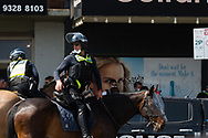 Mounted police are seen directing traffic around the protest during an Extinction Rebellion protest in Melbourne.  A small group of climate protesters marched from Flagstaff Gardens to The Queen Victoria Market and ending with two individuals gluing themselves together, and then glued themselves to Victoria Avenue outside of the Market. This comes as 5 new COVID-19 cases were uncovered in Melbourne's revamped Hotel Quarantine, breaking almost 40 days of virus free days. (Photo by Dave Hewison/Speed Media)