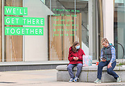 24th February, Cheltenham, England. Two woman sitting on a bench in Cheltenham Town centre during the third national lockdown in England.