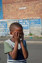 "A young boy tries to hold his mask in place as he prays, in Parkwood, Cape Town, South Africa, on Sunday, May 31, 2020. The joint prayer in Afrikaans opened a special chicken lunch served by the Parkwood Community Upliftment (PCU) project. The youth organization, which normally feeds children as part of an after-school care program, has been feeding children, the elderly, and many other hungry people, in this poverty-stricken area in the Cape Flats since lockdown started more than two months ago. As the nation moves down to Level 3, on June 1st, CPU founder Max Amansure says the organization will continue to feed people. Often it's ""only"" bread as the organization doesn't have any regular funding. However, as the area has been hard hit by COVID-19, Amansure says he wishes Parkwood could have remained on Level 5 Lockdown. PHOTO: EVA-LOTTA JANSSON"
