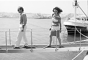 Mort Zuckerman and Diane von Furstenburg walking the plank to Rupert Murdoch's yacht in Tangier harbour. . Malcolm Forbes birthday party. Tangier. 1989.© Copyright Photograph by Dafydd Jones 66 Stockwell Park Rd. London SW9 0DA Tel 020 7733 0108 www.dafjones.com